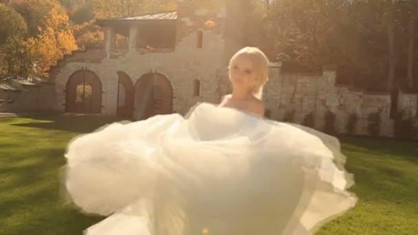 Gyönyörű szőke menyasszony, fehér ruhában pózol a kamera, a középkori vár udvarán