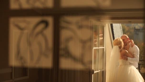 Zadní pohled na krásné nedwlyweds kissingr v luxusní hotel apartmány
