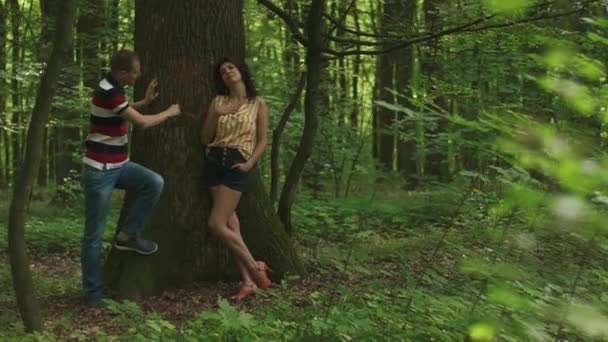 Romantic moment of love. Young beautiful couple in love carving a heart with their initials on a tree. Green spring forest background