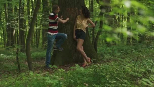 Romantic love story. Young beautiful couple in love carving a heart with their initials on a tree. Green spring forest background