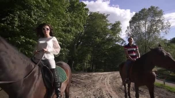 Glückliches junges Paar Reiten im Wald in Bergen