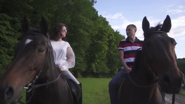 Happy young family couple riding horses together in the green park. Blue sky background