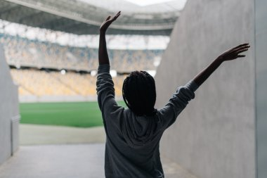 Happy african american woman standing among empty stadium celebrating, her arms raised punching the air with hands, view from back