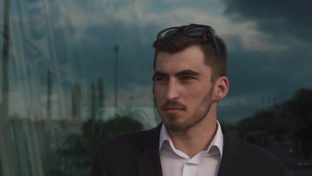 Close-up tvář jistý pohledný elegantní podnikatel mužského modelu zíral na kamera v brýlích. Skleněná stěna pozadí