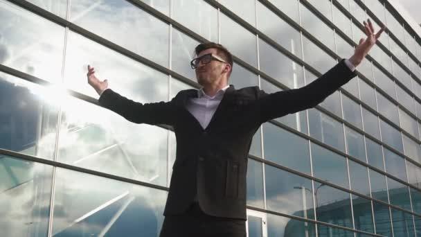 Úspěšný atraktivní podnikatel stál s rukama zvedl se jako vítěz a usmívá se. Skleněná stěna pozadí