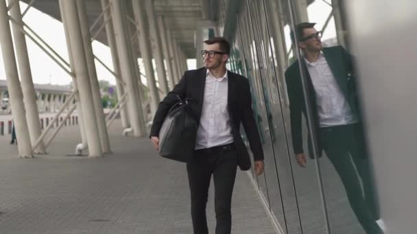 Young businessman pulling suitcase in modern airport terminal. Travelling guy concept