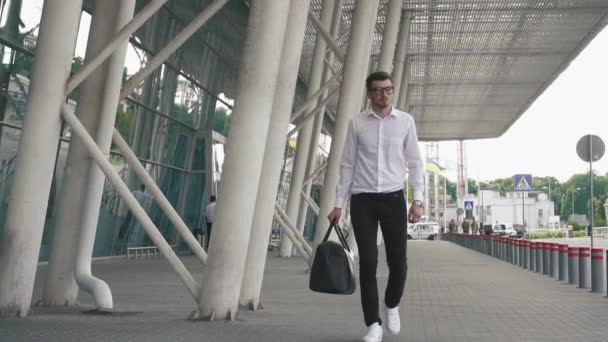 Elegant confident businessman walks in airport hall and carrying his luggage. Business travel concept