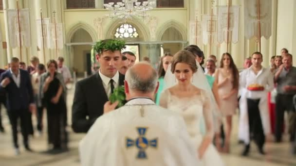 Wedding couple wearing green laurel wreathes in the church during wedding ceremony. 31.08. 2015, Church of Sts. Olha and Elizabeth, Lviv, Ukraine