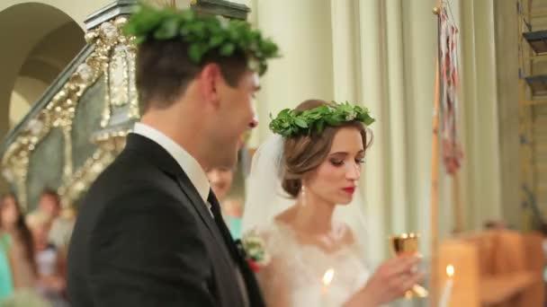 Ifjú visel zöld laurel wreathes a templom esküvő alatt. Menyasszony italok bor kehely