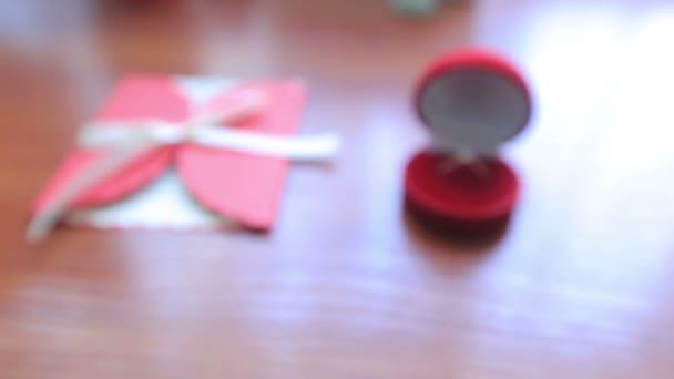 Dolly záběr snubní prsten v červený krabici a pohlednice na stůl