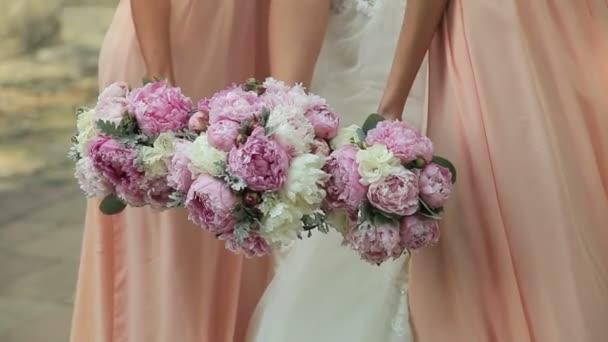 Nevěsta a dvě družičky pózuje s kytičky