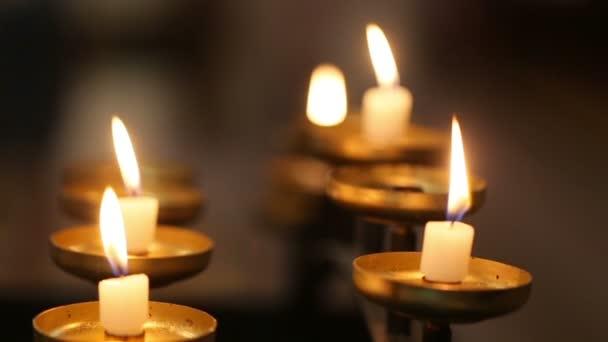 Žluté svíčky hoří ve tmě zblízka. Symbol oslav