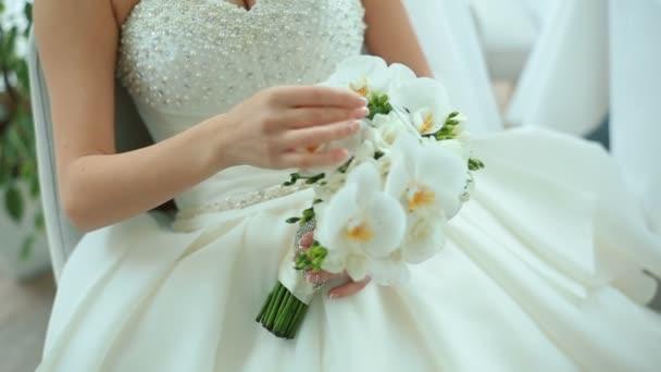 Krásná nevěsta drží bílé svatební kytice. Svatební doplňky. Podrobnosti o manželství