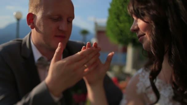 Vőlegény halkan megérinti a menyasszony kezét közelről. A háttérben a Comói-tó, Olaszország