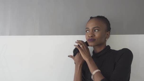 Porträt von lächelnden jungen Afrikanerin mit leuchtend violetten Lippen wegsehen auf grauem Hintergrund