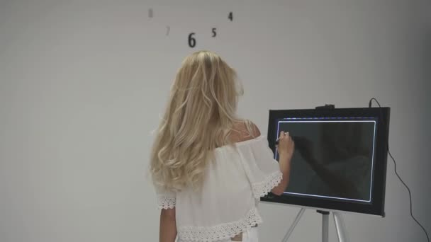 Attractive blonde girl in white top tries to draw logo for dental health company