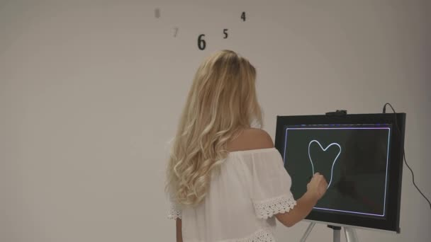 Attractive blonde woman in white top tries to imagine logo for dental health company