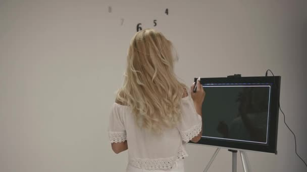 Attractive blonde woman in white top tries to draw logo for dental health company