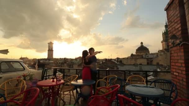 Mladý pár milující něžně líbat na střešní kavárnu s výhledem na starobylé město za deště. Romantický západ slunce s oblohy v mracích na pozadí