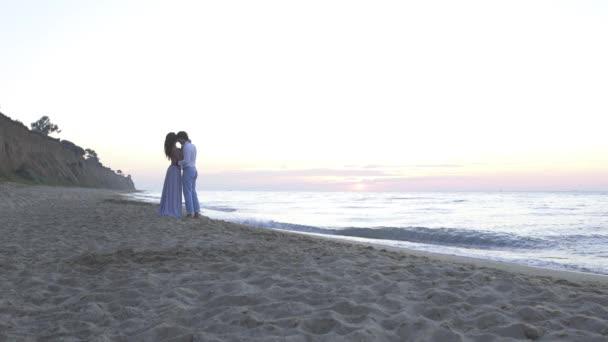 Atraktivní enloved mladý pár líbání na pláži na večer. Romantické líbánky koncept