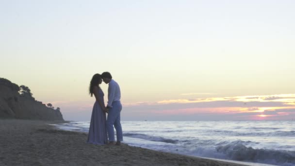 Attractive enloved young couple have a sweet romantic moment on the beach at evening. Romantic honeymoon concept