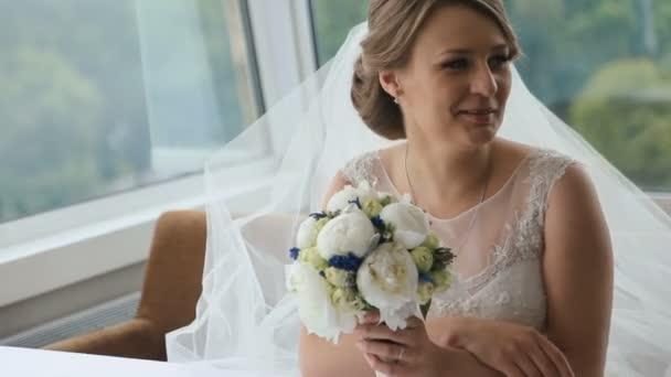Šťastná blondýnka se svatební kyticí, která sedí v kavárně u stolu