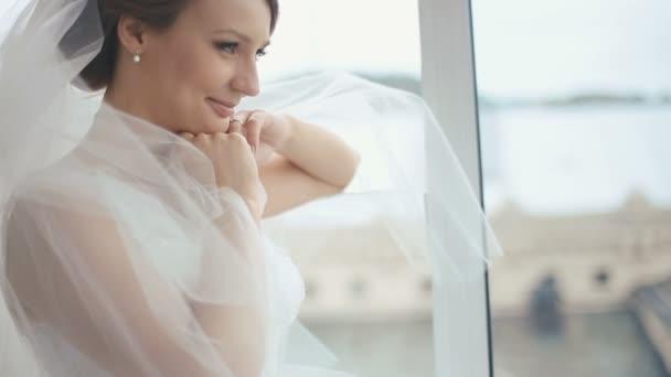 Szép szőke menyasszony fehér ruhában jelentő és szép mosolygós az ablak közelében a kávézóban