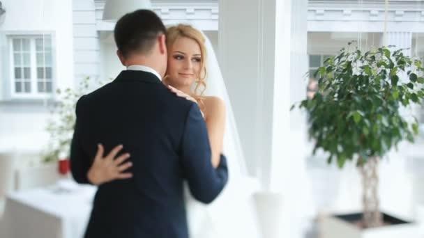 Nádherná nevěsta a ženich jemně objímá na jejich svatební oslavu v luxusní restauraci