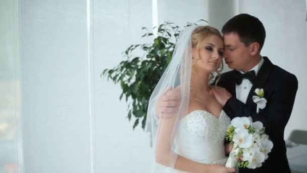 Okamžik něžnosti. Okouzlující nevěsta a ženich jemně objímá na jejich svatební oslavu v luxusní restauraci