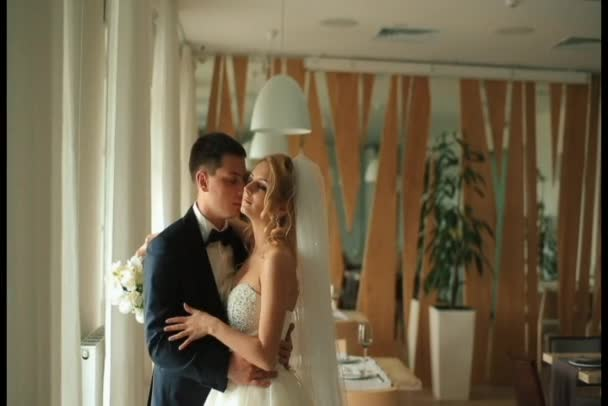Magnificent bride and groom softly kissing on their wedding celebration in the luxury restaurant