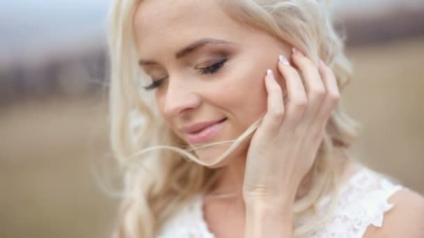Close up of magical beautiful young blonde bride softly touching her face. Outdoor blurred background