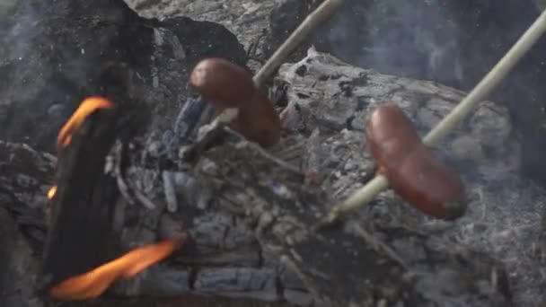 Two sausages attached to sticks are baking on flame of campfire