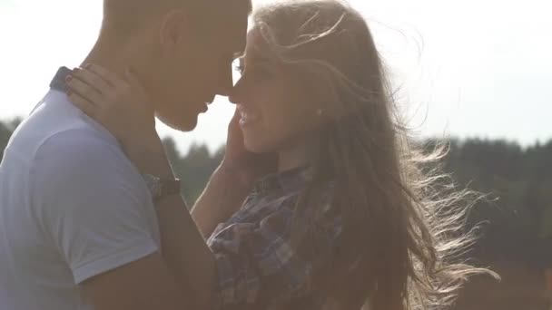 Close up teenager couple in love kissing outdoor at bright sunny day. Light breeze waving girls hair. Warm filter tone