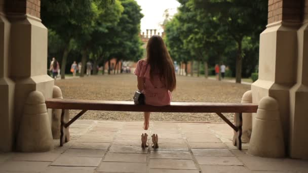 Teenage girl sitting down on bench in nature and reading a book barefoot with legs crossed. Back view