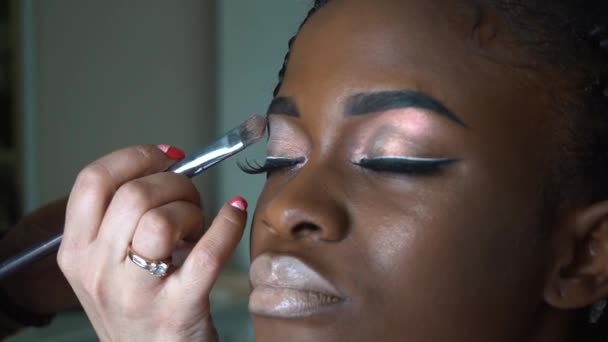 Makeup artist makes a bright makeup for beautiful african american girl   Close-up