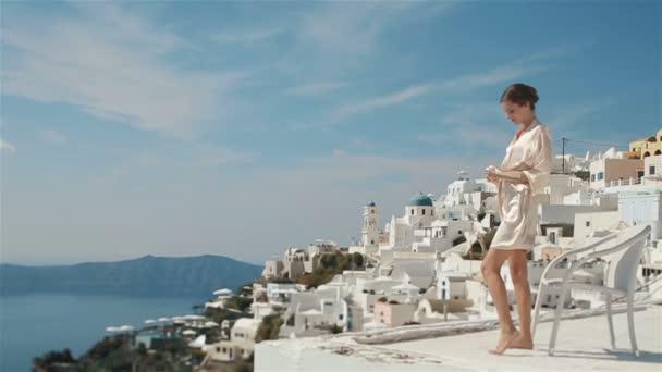 Krásná sexy bruneta nevěsta v županu seděla na střeše s nohama zkříženýma a užívajícími si výhled na hory a moře