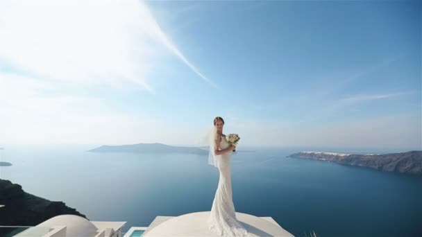 Beautiful sexy brunette bride in wedding dress with bouquet in her hands  standing at the roof and enjoying the amazing view