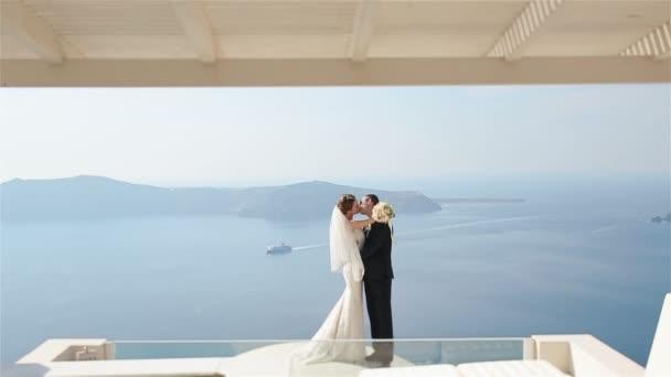 Felice coppia sposata che bacia sulla terrazza con il fondo del mare, Santorini closeup