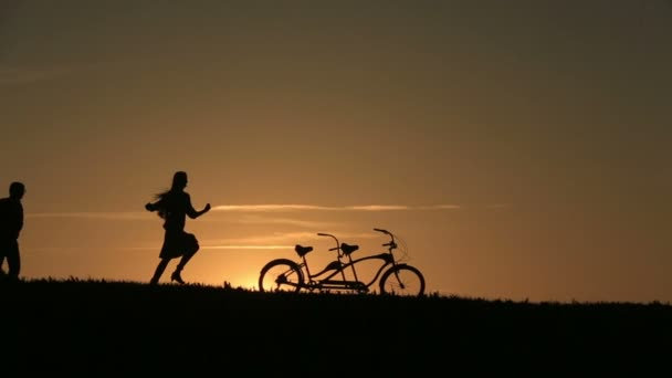 Silhouette of  Beautiful Couple With Tandem Bicycles Playing Catch  Against  Sunset On The Backgrund Close Up