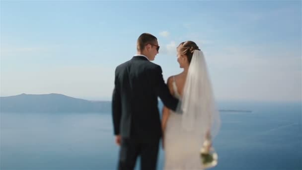 Happy married couple kissing on terrace with sea background, Santorini closeup