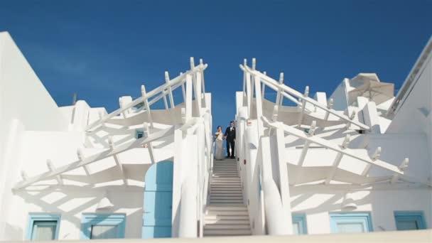 Marito e moglie newlywed venire giù per le scale bianche dalla navata di matrimonio con il cielo su priorità bassa
