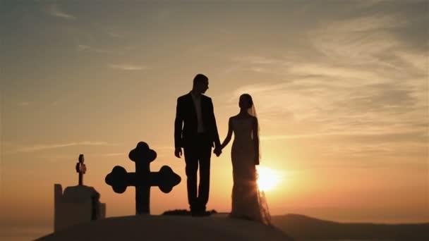 Šťastný manželský pár walkiing, drželi se za ruce a líbání na střechu kostela na pozadí nebe