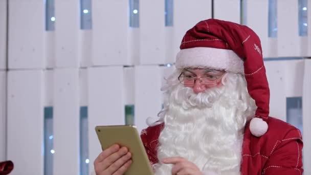 Santa Claus Use digitální Tablet v místnosti s vánoční stromek a dárky