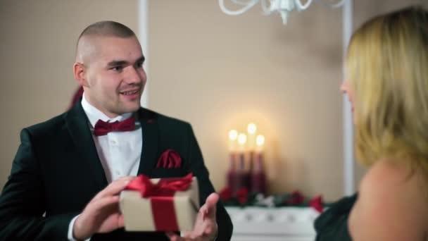 Muž v černém obleku dává žena v dárkové černé večerní šaty s červenou stužku žena třese dar v bílé místnosti s krbem a vánoční stromeček