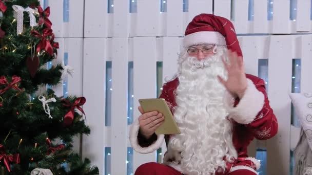 Santa Claus Is ülni és ujj, akár digitális tabletta, szoba, kandallóval és a karácsonyfa, ajándékok.