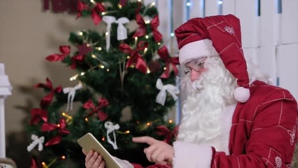 Santa Claus oldal bekapcsolja a szobában a karácsonyfa és az ajándékok digitális tabletta