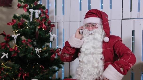 Mikulás ülni, és beszélni a telefon, Room, kandallóval és a karácsonyfa, ajándékok.