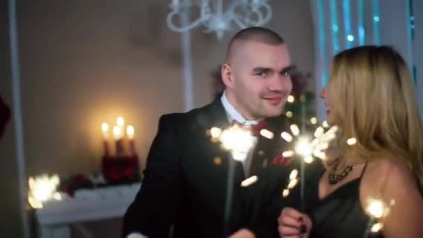 a Man in a Black Suit and a Woman in Evening Black dress dancing with sparklers, big smile, in a white room with fireplace and Christmas tree