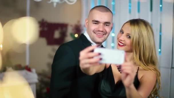 Žena v večerní černé šaty dělá fotky na The Smartphone muž v černém obleku v bílé místnosti s krbem a vánoční stromeček