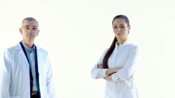 Doctor Approaches Nurse in White Studio, They Look at the Camera and Smile